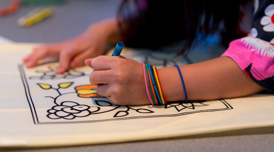 Girl coloring an Ojibwe shoulder bag activity kit