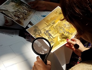 Photo of a teacher investigating a political cartoon using a magnifying glass.