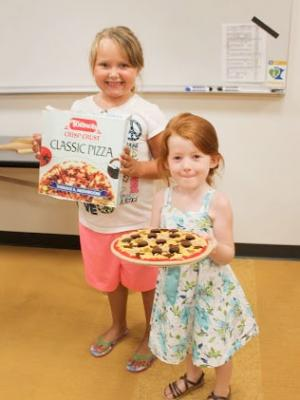 Two girls holding frozen pizza with box
